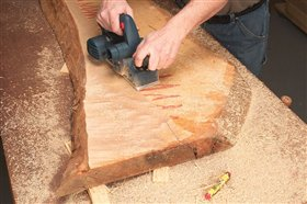 2. Plane the high spots down to the line using a handheld power planer. First use a lumber crayon to mark the high areas. Skew the planer so the heel rides on the previously cut surface. Cut with the grain to avoid tear-out. Check your progress frequently with a straightedge.