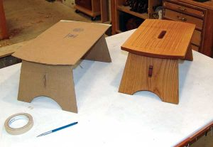 The beginning and the end. The completed stool in solid wood next to the cardboard mock-up.