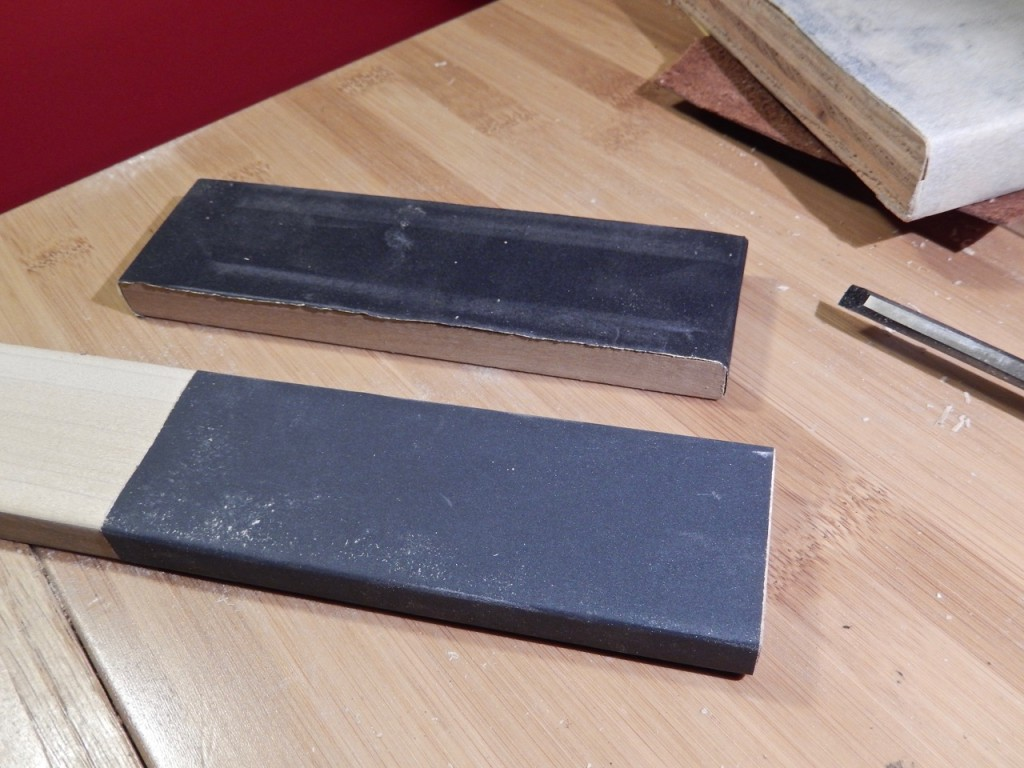 I found that wrapping and anchoring the sandpaper around the length of the plate (see lower sandpaper plate in the following image) will give you better results.