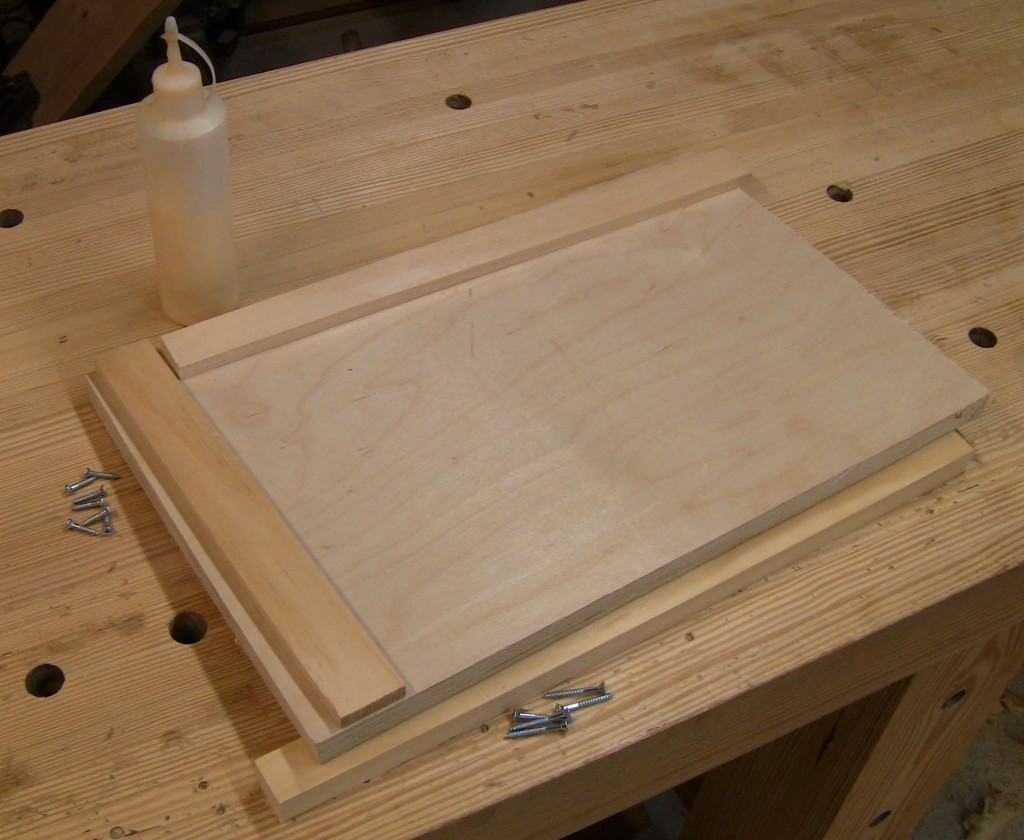 "Parts for a smaller board: 12"" x 18"" base of 3/4"" plywood, 1 1/4"" wide topside stop strips of solid wood resawn to 3/8"" thick, 1"" wide underside stop strip of 3/4"" solid, glue, and screws."