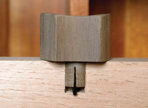 Foxed wedge. If your handle is attached with a dowel, you can wedge it in place by cutting a slot and then insert a wedge loosely in the slot. When the handle fully seats and the dowel bottoms out in the hole, the wedge will be pushed farther into the dowel and spread it for a tight fit.