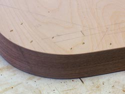 Walnut veneer, applied using contact cement, covers the face of the base's curved front and side edges.