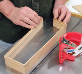 Using packaging tape to glue up a mitered box.