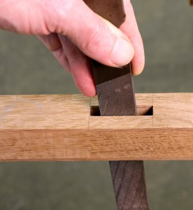 Clean edges of a mortise with a plastic laminate file