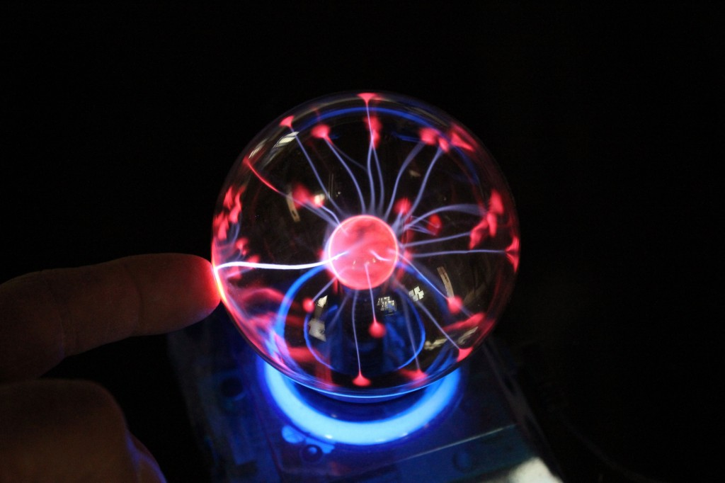 Charged electrons try to escape the plasma globe at the point of contact with a conductive body (Steve's finger).