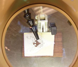 Reverse direction. To cut out the inlay, feed the piece to the saw blade in the opposite direction.