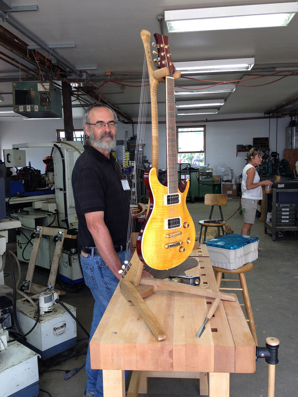 Luthier Patrick Sebrey with one of his guitars and stands