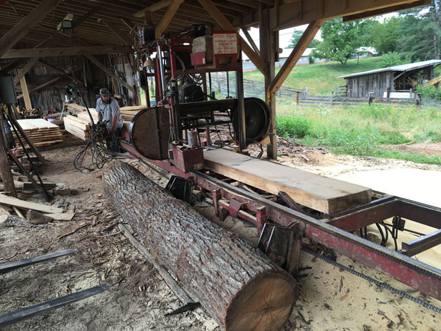 Lesley Caudle running his band saw mill.