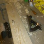 Cutting a bevel on a piece of trim with a handplane. This is a practice piece with a big knot in the middle.